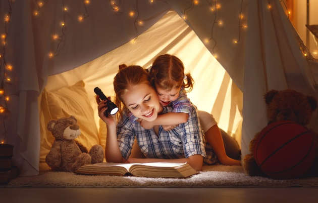 mother and child daughter with a book and a flashlight before going to bed